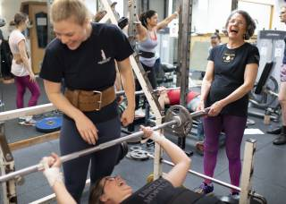 Women powerlifting in gym.  In the foreground, three women are laughing at a bench press station: one is preparing to bench press and the others are spotting.  In the background, at a squat rack, other women are chatting between lifts