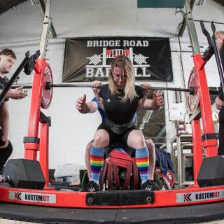 Woman in Linacre Ladies powerlifting kit and rainbow socks in mid-squat in competition