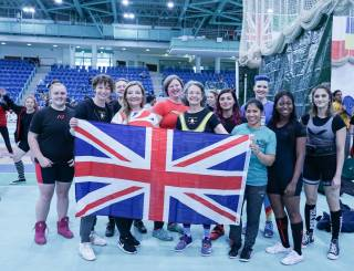 A group of smiling women in powerlifting kit hold a British flag; background is a large auditorium