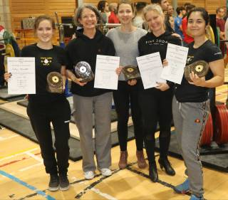 Five women in gym holding trophies and certificates